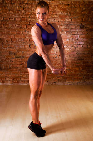 strong woman is posing against brick wall photo