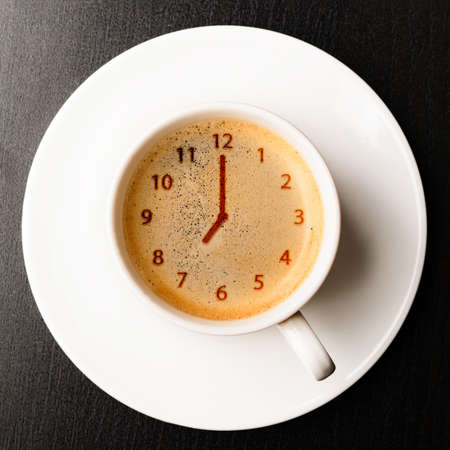 light breakfast: clock  cup of fresh espresso with clock sign, view from above Stock Photo