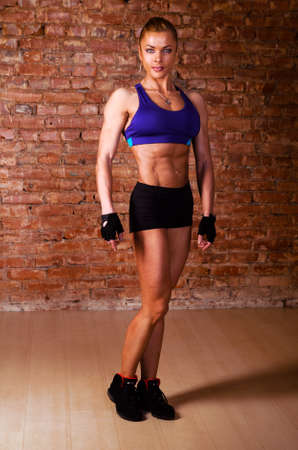 female muscle: strong woman is posing against brick wall