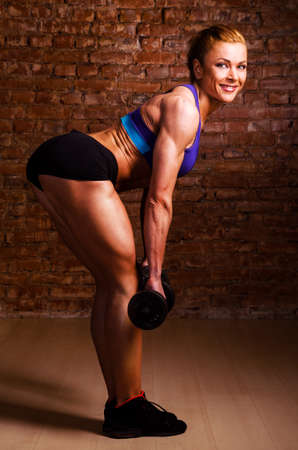 female muscle: strong woman is training with barbells