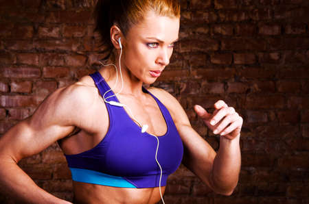 cardio fitness: strong woman is running and listening music