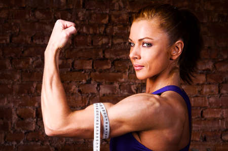 strong woman is measuring her biceps photo