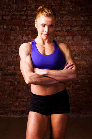 tank top: strong woman is posing against brick wall