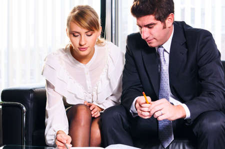 two business persons are sitting and discussing on leather sofa at office Stock Photo - 18676325