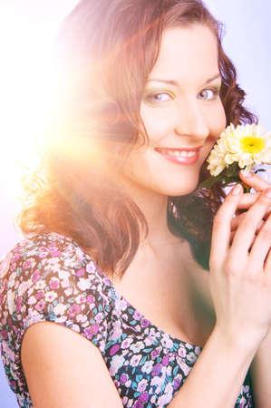 beautiful woman with big flower in sun rays photo
