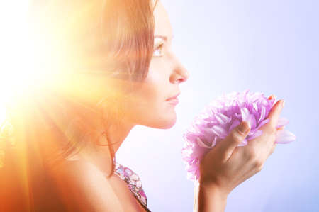 beautiful woman with big flower in sun rays Stock Photo