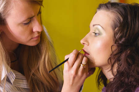 fashion shoot: makeup artist is applying cosmetics on model face