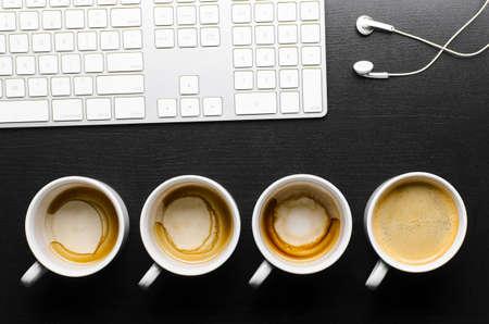 trompo de madera: las horas de trabajo tazas vac�as y llenas de caf� fresco con teclado y auriculares, vista desde arriba