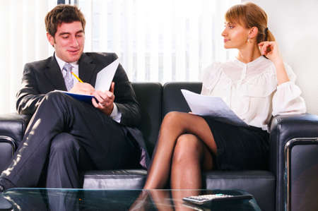 abreast: two business persons are sitting and discussing on leather sofa at office