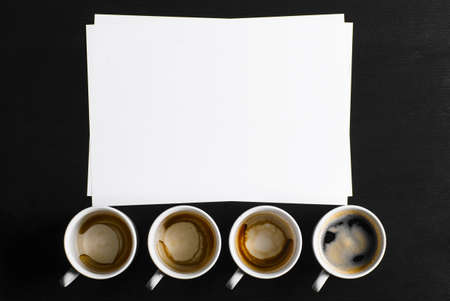 business creativity concept  empty and full cups of fresh espresso with blank paper on desk photo