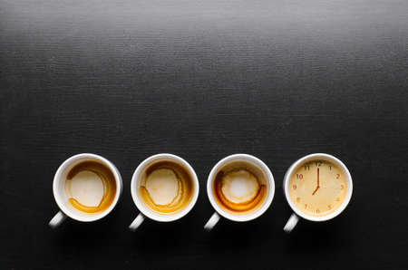 working hours  empty and full cups of fresh espresso with clock sign, view from above Stock Photo