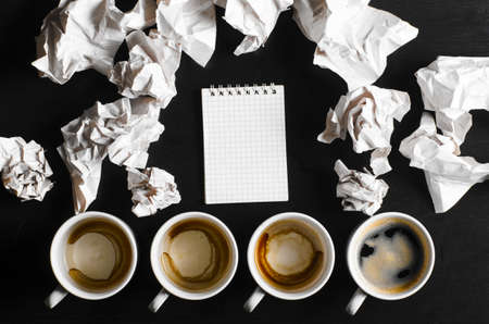 crumpled sheet: business creativity concept  empty and full cups of fresh espresso with crumple wads on desk Stock Photo