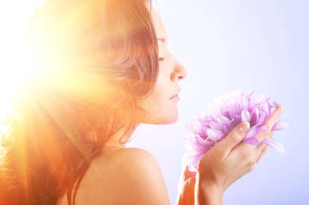 sunny day: mujer hermosa con la flor grande en rayos del sol