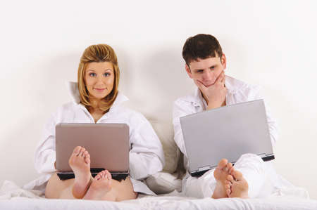 man and his pregnant wife in bed at morning with laptops photo