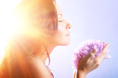 beautiful woman with big flower in sun rays photo