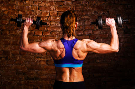 bicep: strong woman is training with barbells