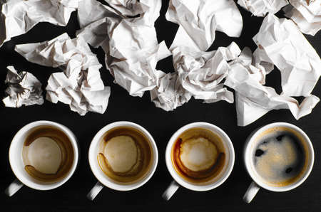 office space: business creativity concept  empty and full cups of fresh espresso with crumple wads on desk Stock Photo