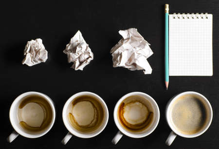 business creativity concept  empty and full cups of fresh espresso with crumple wads on desk photo