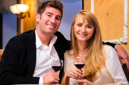 laughing embracing couple is sitting at restaurant and drinking wine photo