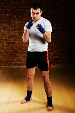 powerful man: portrait of mma fighter in boxing pose against brick wall Stock Photo