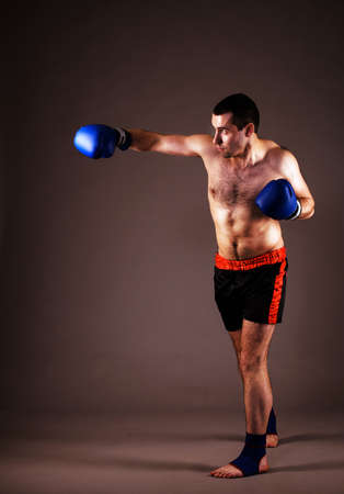 portrait of mma fighter in boxing pose on gray background photo