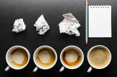 business creativity concept  empty and full cups of fresh espresso with crumple wads on desk Stock Photo