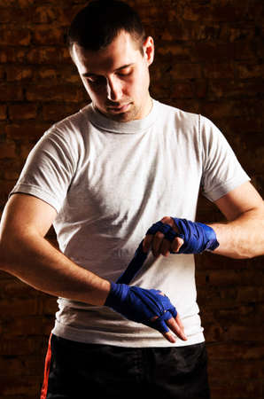 boxing tape: mma fighter is getting ready against brick wall