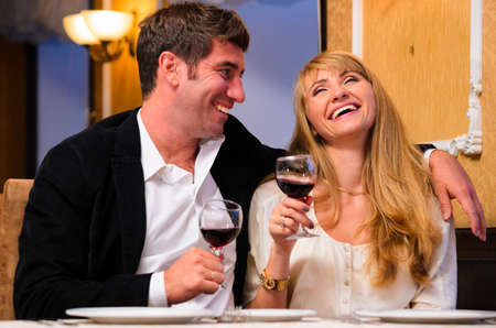 laughing embracing couple is sitting at restaurant and drinking wine Stock Photo - 19671852