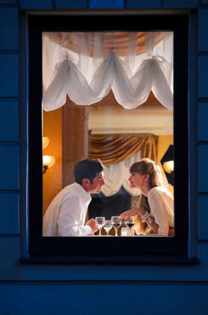 a meeting with a view to marriage: smiling couple is sitting at restaurant, view from street Stock Photo
