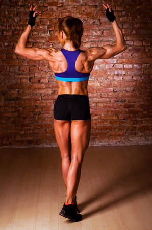 back muscles: strong woman is posing against brick wall