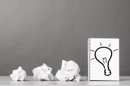 reciclaje de papel: tacos arrugados proceso creativo y el cuaderno con la imagen del bulbo