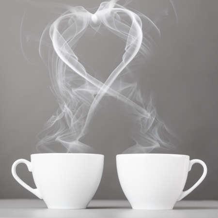 liefde en koffie hart silhouet van dampende koffie kopjes Stockfoto