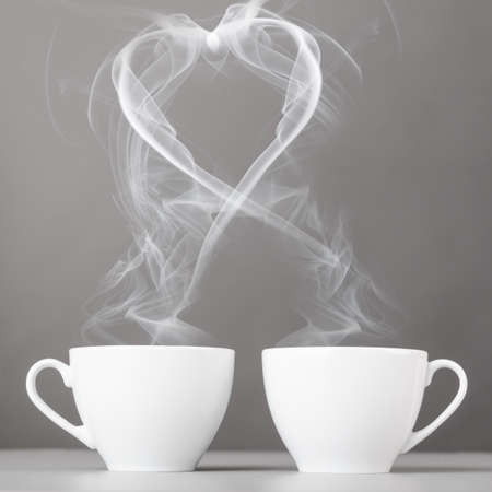 love and coffee  heart silhouette from steaming hot coffee cups photo