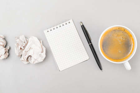 creative process  crumpled wads, blank notebook and cup photo