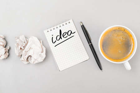 creative process  crumpled wads, notebook with idea word and cup photo