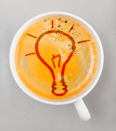 tip up: idea  cup of fresh espresso with bulb sign, view from above