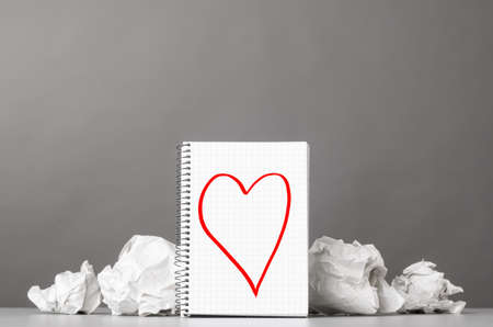 creative process  crumpled wads and notebook with heart picture photo