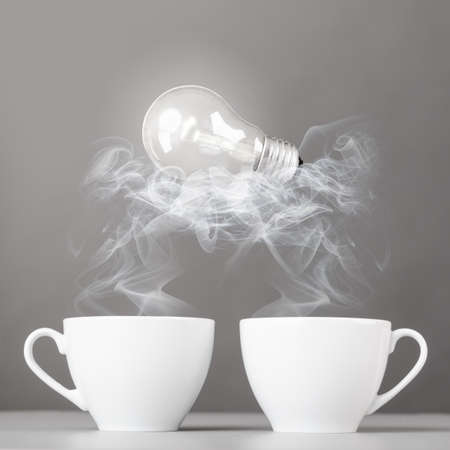 idea birth  bulb is lying on steaming hot coffee cups photo