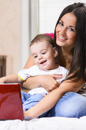 mother and son are using laptop at home photo