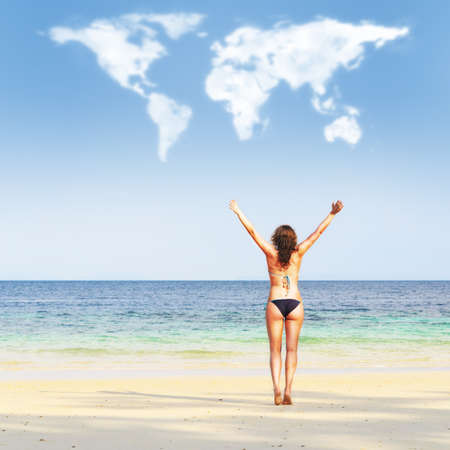loving travelling  young woman on beach is trying to embrace continents shaped clouds photo