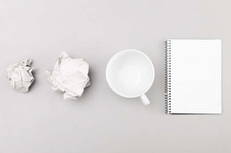 creative process  crumpled wads, notebook and cup on gray photo