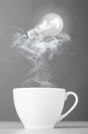 steaming coffee: idea  bulb is lying on steaming hot coffee cup
