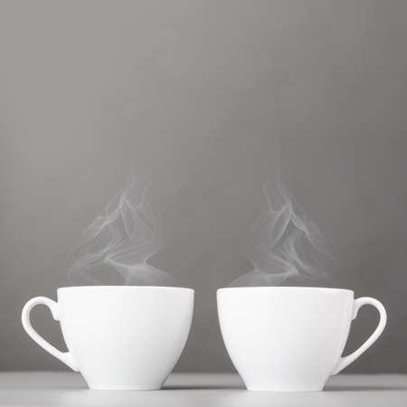 kopjes hete koffie op een grijze achtergrond Stockfoto