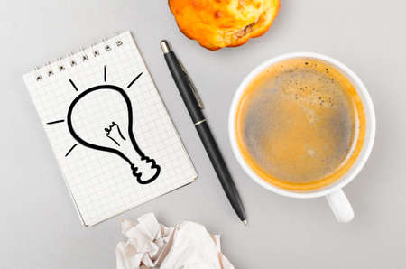 creative process  crumpled wads, notebook with bulb picture and cup photo