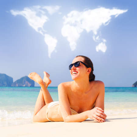 loving travelling  young woman is lying on beach under continents shaped clouds photo