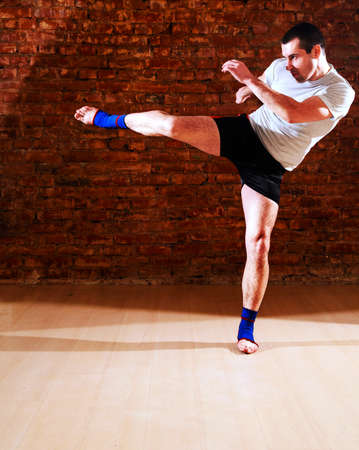 kick boxer: portrait of mma fighter in boxing pose against brick wall Stock Photo