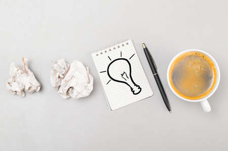 creative process  crumpled wads, notebook with bulb picture and cup