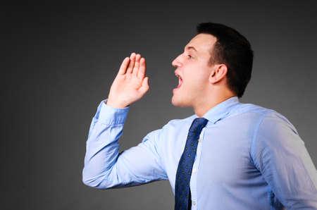 man side: businessman is screaming on dark background