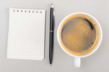 creative process  blank notebook and cup on gray photo