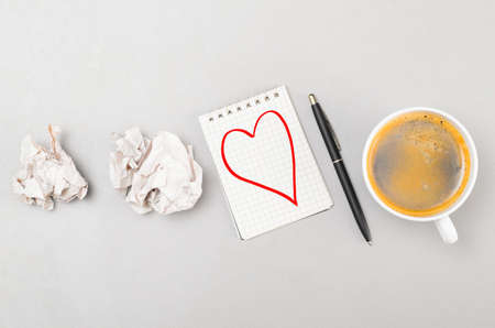 love letter  crumpled wads, notebook with heart picture and cup photo